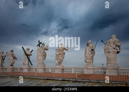 Stormy skies over the statues along the roof-line of Saint Peters Basilica, Vatican, Rome, Italy - Stock Photo
