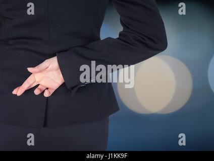 Digital composite of Woman with fingers crossed. Lights blurred background - Stock Photo