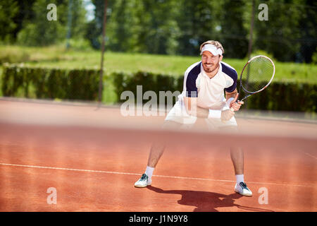 Male tennis player with racket in action on tennis court - Stock Photo