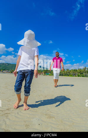 Father and son walking along beach. Boy's face hidden under the hat - Stock Photo