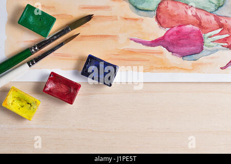 Still life watercolor paint. Vegetables on the kitchen table. Brush and paint in the cuvettes close-up. - Stock Photo