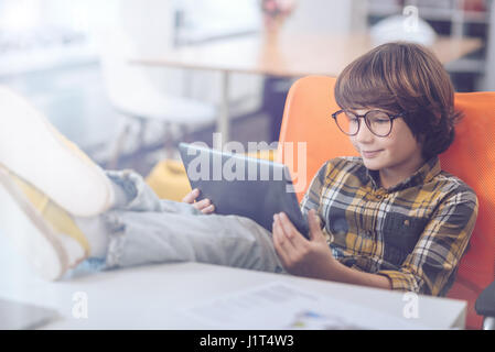 Boy using digital tablet with feet up - Stock Photo