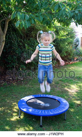 YOUNG GIRL PLAYING ON TRAMPOLINE IN GARDEN (model release -  Editorial use only) - Stockfoto