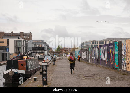 Man running beside Union canal near Toll Cross in Edinburgh, Scotland, UK, Britain. Weather: overcast day with sunny - Stock Photo