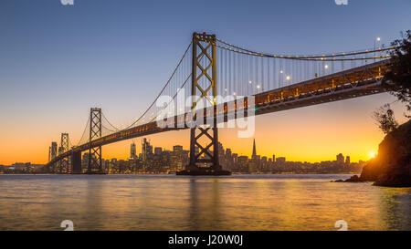 Classic panoramic view of San Francisco skyline with famous Oakland Bay Bridge illuminated in beautiful golden evening - Stock Photo