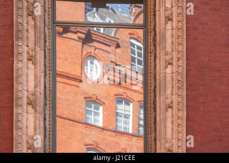 reflection of an old brick building in london in an a window with elaborate molding - Stock Photo