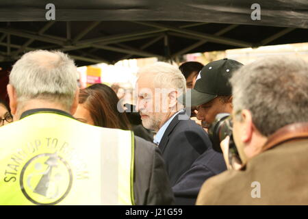 London, UK. 23rd April, 2017. Labour Party leader, Jeremy Corbyn is helped through crowds as he leaves after speaking - Stock Photo