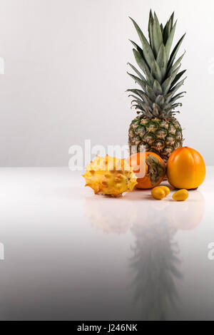 Vertical shot of tropical fruit composition on a white surface with reflection on it - Stock Photo