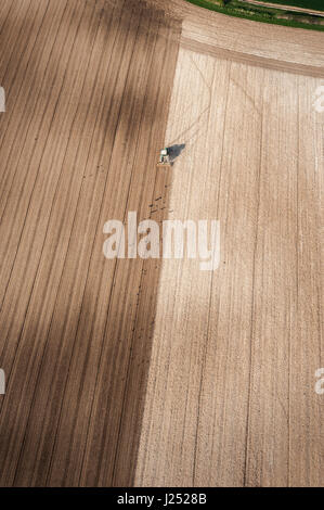 AERIAL VIEW of agriculture crops and farmland ploughed by tractor - Stock Photo