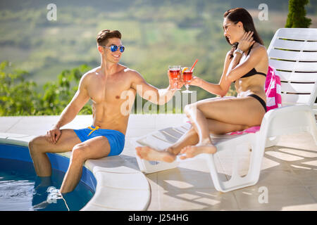 Young couple enjoying in cocktails  next swimming pool - Stock Photo