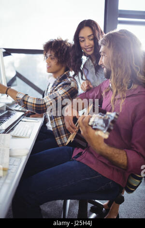 Three sound engineers working together in the studio - Stock Photo