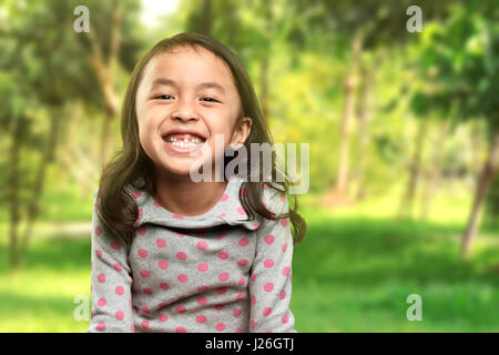 Funny asian little girl smile with her broken tooth in the park - Stock Photo