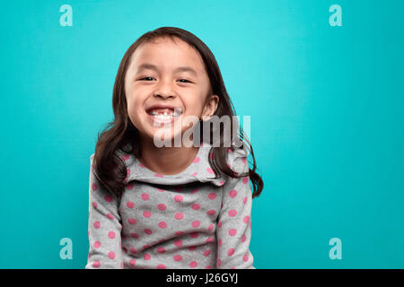 Smiling asian little girl and her broken teeth over blue background - Stock Photo