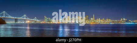 Classic panoramic view of the skyline of San Francisco with famous Oakland Bay Bridge  illuminated in beautiful - Stock Photo