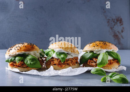 Homemade mini burgers with pulled chicken, basil, mozzarella cheese and yogurt sauce on baking paper over gray texture - Stock Photo