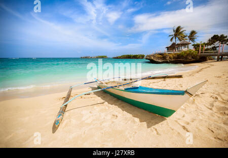 Philippines traditional fishing boat in the clear sea waters on the blue sky background with shining sun - Stock Photo