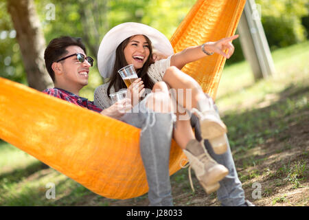 Smiling girl in hammock show with finger something to her boyfriend  in woods - Stock Photo