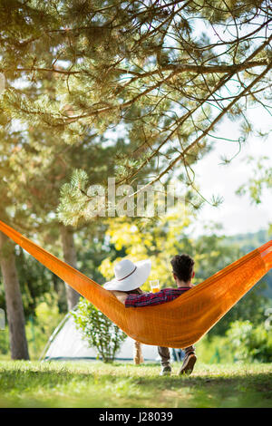Embracing couple in hammock from back on picnic in woods - Stock Photo