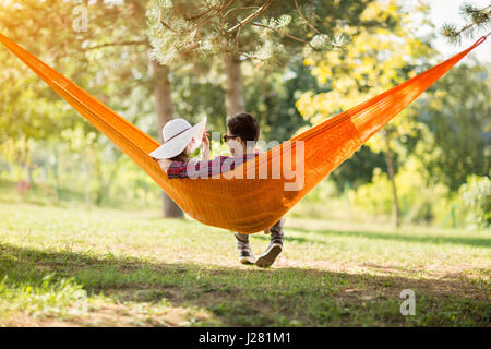Young man and woman on hammock in green nature from back - Stock Photo
