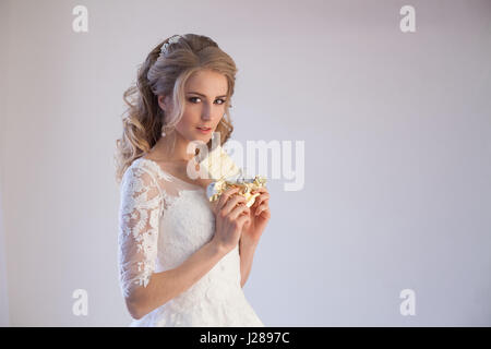 bride in wedding dress holding a chocolate - Stock Photo