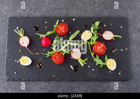 Fresh radish, cherry tomato, quail egg, ruccola with balsamic glaze on a black stone plate. Mediterranean lifestyle. - Stock Photo