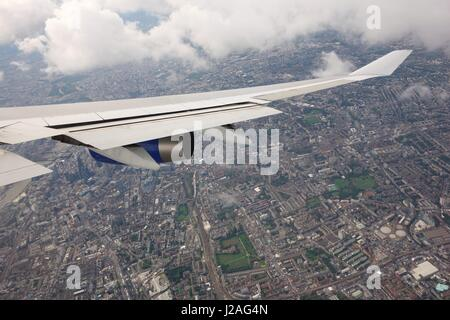 Wing of a jet passing over North east of London on route to Heathrow Airport. - Stock Photo
