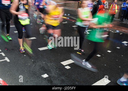 Participants taking part in the London Marathon running some four miles to go to complete the race on 23rd April - Stock Photo