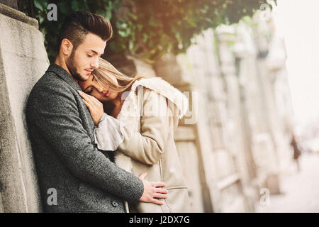 Portrait of beautiful young couple outside. Couple in love outdoor on street.Added photo filter and grain/noise. - Stock Photo