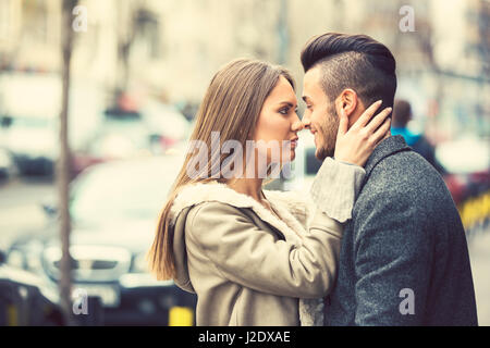 Portrait of beautiful smiling young couple outside, side view face to face. Happy couple in love outdoor on street.Added - Stock Photo