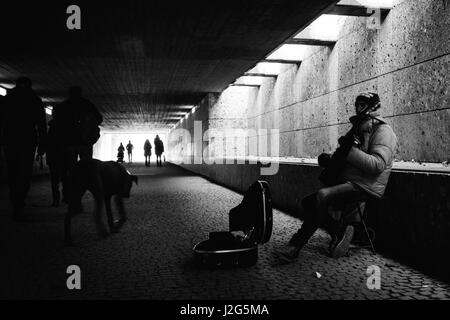 Street busker / musician playing a  guitar for money in a pedestrian underpass in Munich, close to the English Garden. - Stock Photo