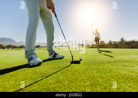 Low angle view of golfer on putting green about to take the shot. Male golf player putting on green with second - Stock Photo