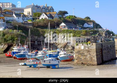 Newquay, Cornwall, UK - April 1 2017: Colourful fishing and sailing boats on the sand in Newquay harbour at low - Stock Photo