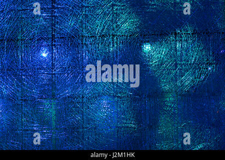 Macro shot of a transparent textured background, illuminated with colour lights - Stock Photo