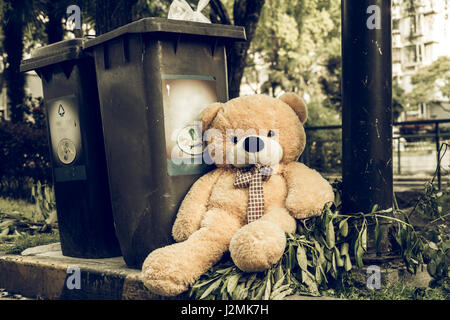 The teddy-bear was throw away sitting byside the garbage trash - Stock Photo