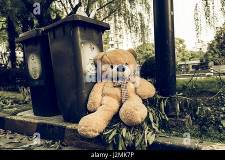The teddy-bear was throw away sitting beside the garbage trash - Stock Photo