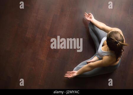 Young yogi woman practicing yoga, sitting in Half Lotus exercise, Ardha Padmasana pose, working out, wearing sportswear, - Stock Photo
