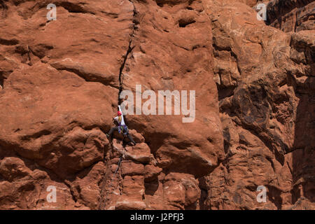 Woman rock climber cliffs in Arches national Park, Utah - Stock Photo