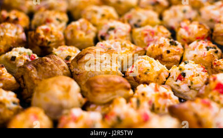 Appetizing baked little puff pastry stuffed with crabmeat, lined in rows - Stock Photo