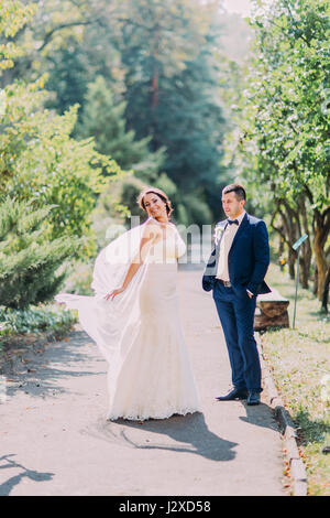 The photo of happy newlyweds. The bride in white dress is moving around while her groom is standing nearby - Stock Photo
