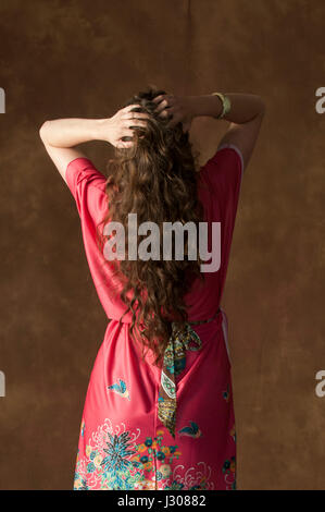 Rear view of a stressed young woman wearing a vintage red gown head in hands - Stock Photo
