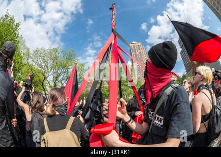 New York, USA. 01st May, 2017. New York, NY 1 May 2017 - Anarchists dance around a Maypole at a May Day/International - Stock Photo