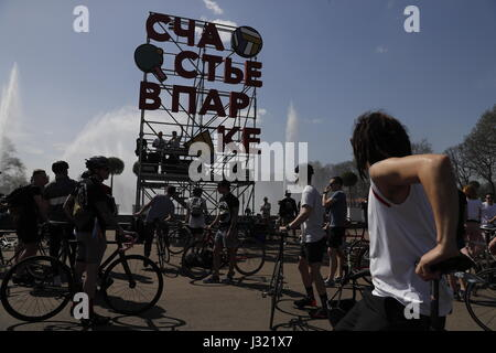 Moscow, Russia. 1st May, 2017. Cyclists by a sign reading 'Happiness in the park' in Moscow's Gorky Park. Credit: - Stock Photo