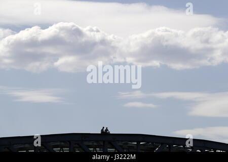 Moscow, Russia. 1st May, 2017. People sit atop Pushkinsky bridge spanning the Moskva River. Credit: Artyom Geodakyan/TASS/Alamy - Stock Photo