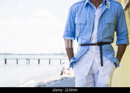 Handsome Indian man posing in a vacation context. Street fashion and style. - Stock Photo