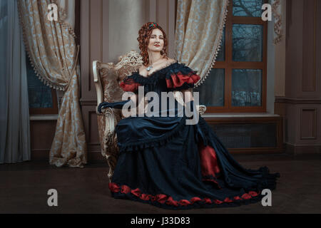 Woman in Victorian dress sitting on a chair in the room. - Stock Photo