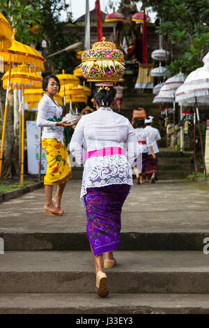 UBUD, INDONESIA - MARCH 2: Woman with basket on the head  walks up the stairs during the celebration before Nyepi - Stock Photo
