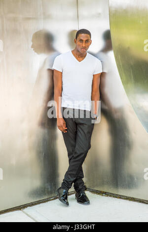 Street Fashion. Young African American Man wearing white V neck T shirt, black pants, leather shoes, hand in pocket, - Stock Photo