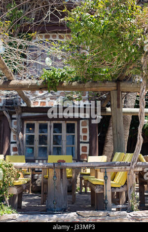 A Small Wooden Summer House With Chairs A Table And A