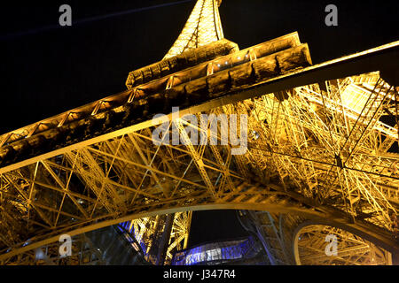 Perspective view from down to the top of the Eiffel Tower at night, Paris - Stock Photo