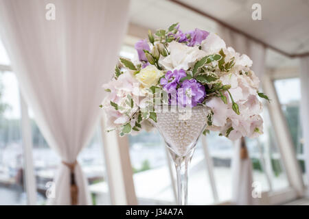 A bouquet of flowers in a glass vase on the dining table, decoration of the wedding - Stock Photo